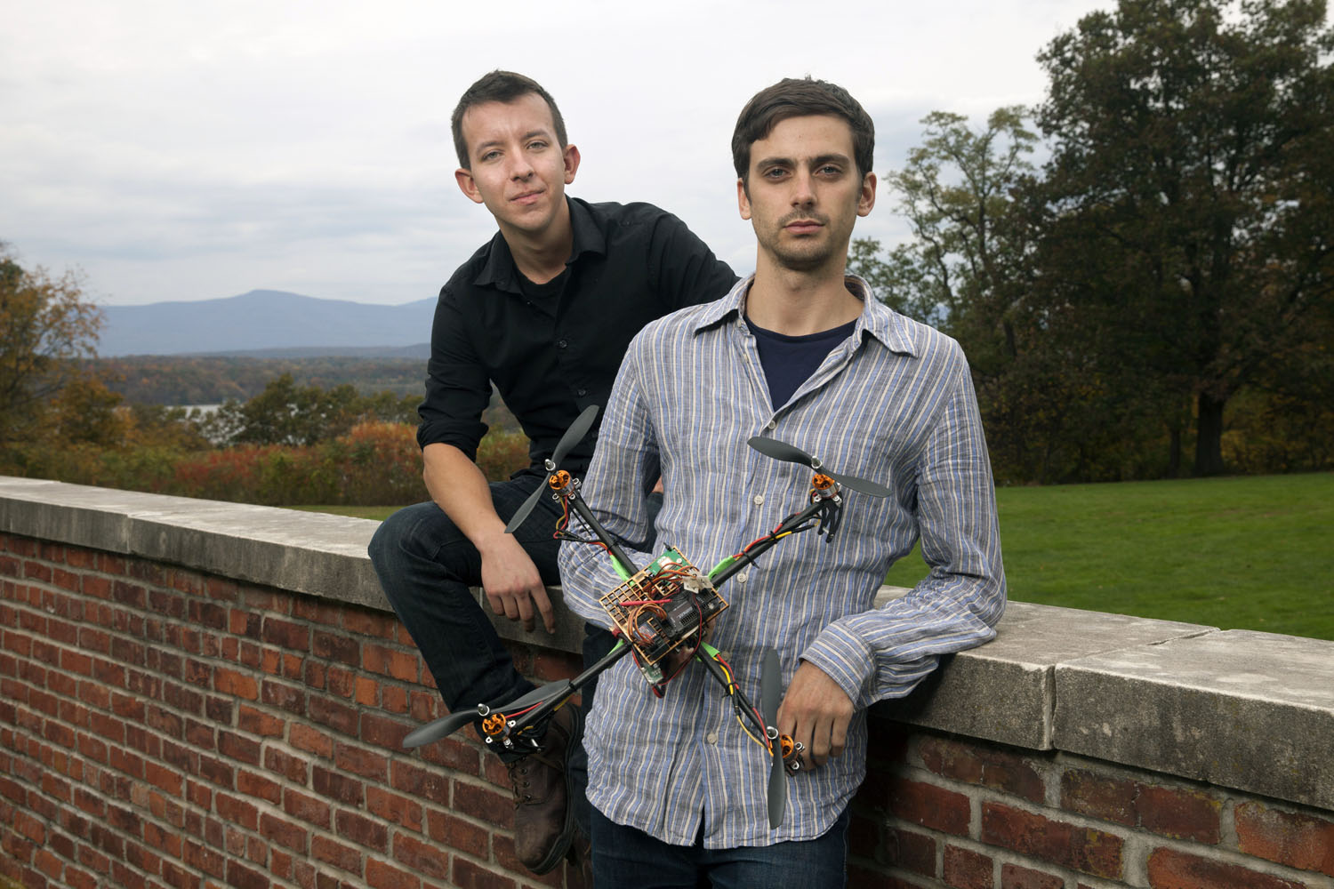 Dan Gettinger '13 (left) and Arthur Holland Michel '13, holding astudent-built drone.